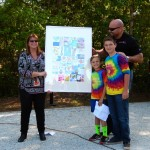 CMCS students present Stella and Larry Mercado with a thank-you gift of student-created art.
