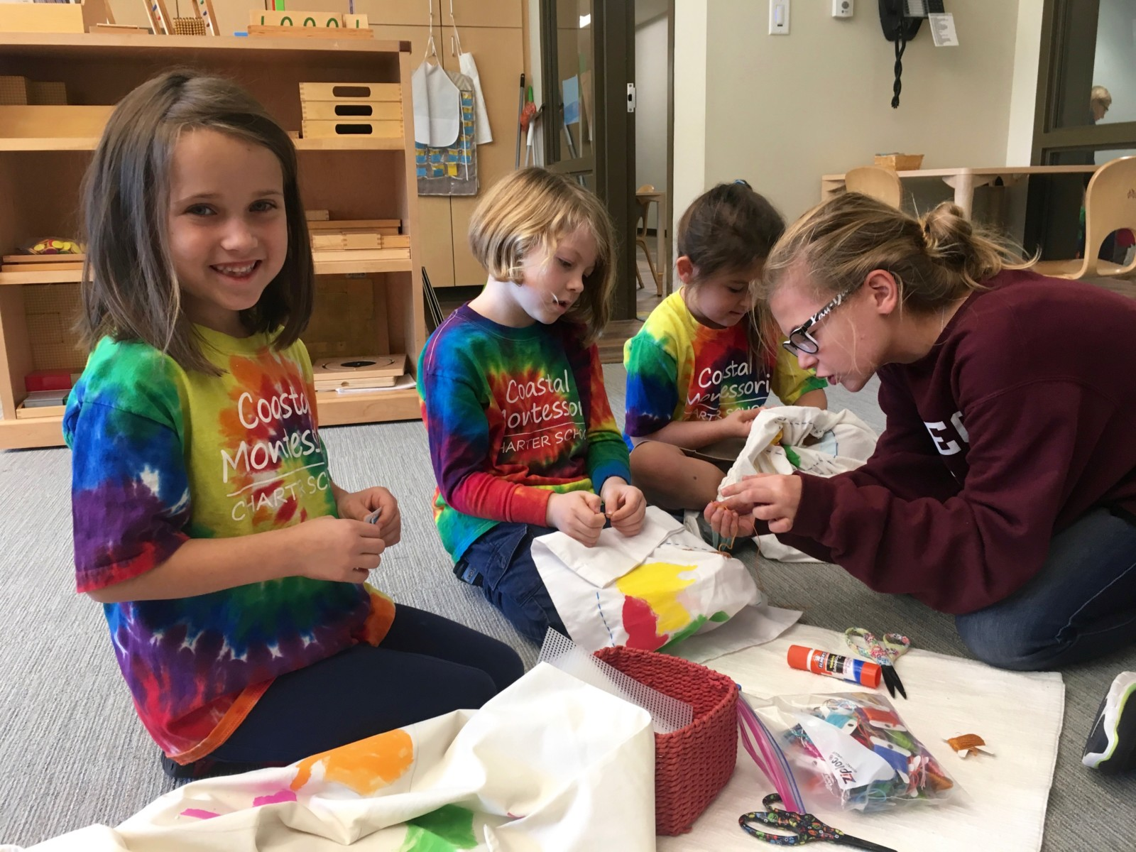 Elementary students learn sewing from a middle school student in a Montessori classroom