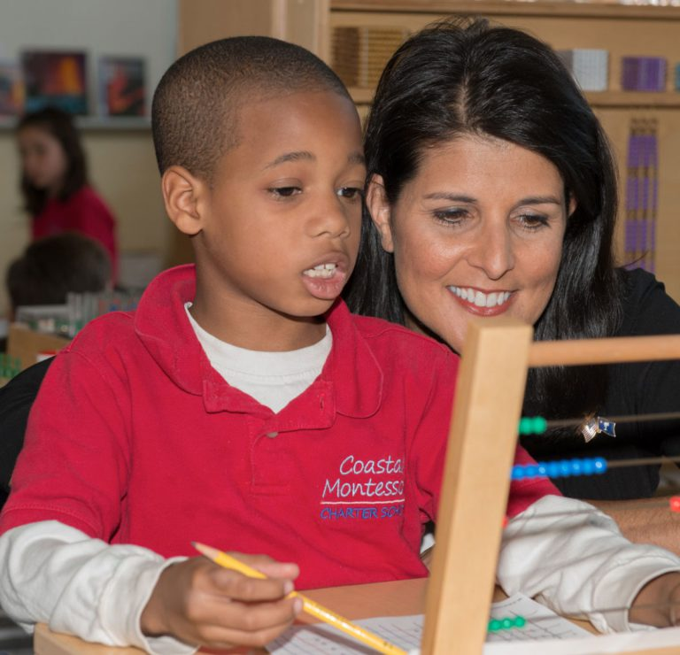 Politician Nikki Haley and student looking at an abacus