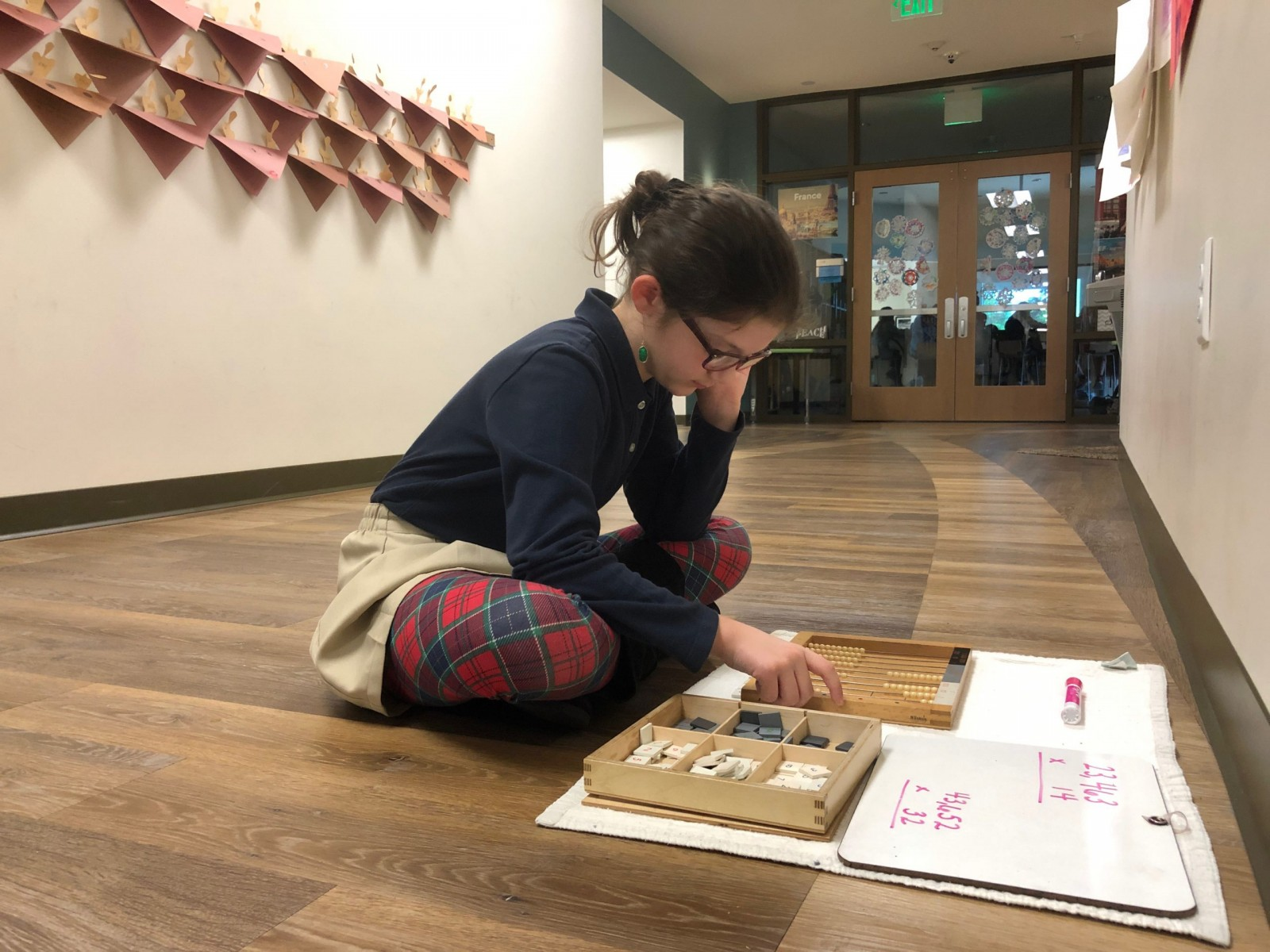 Girl utilizing freedom of movement, working on Montessori materials in the hallway