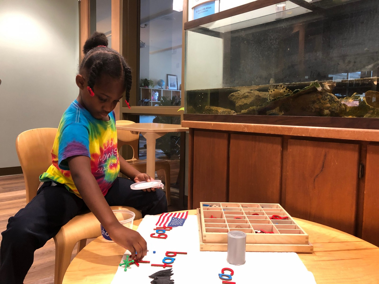 Lower Elementary student working on Montessori materials next to a fish tank with a swimming turtle
