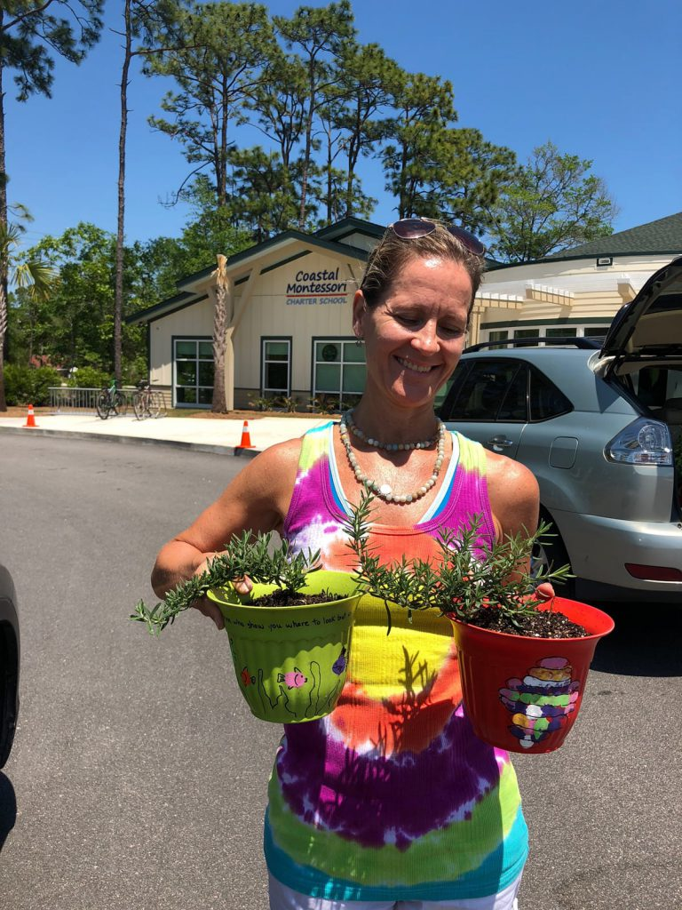 Volunteer hold plants outside school