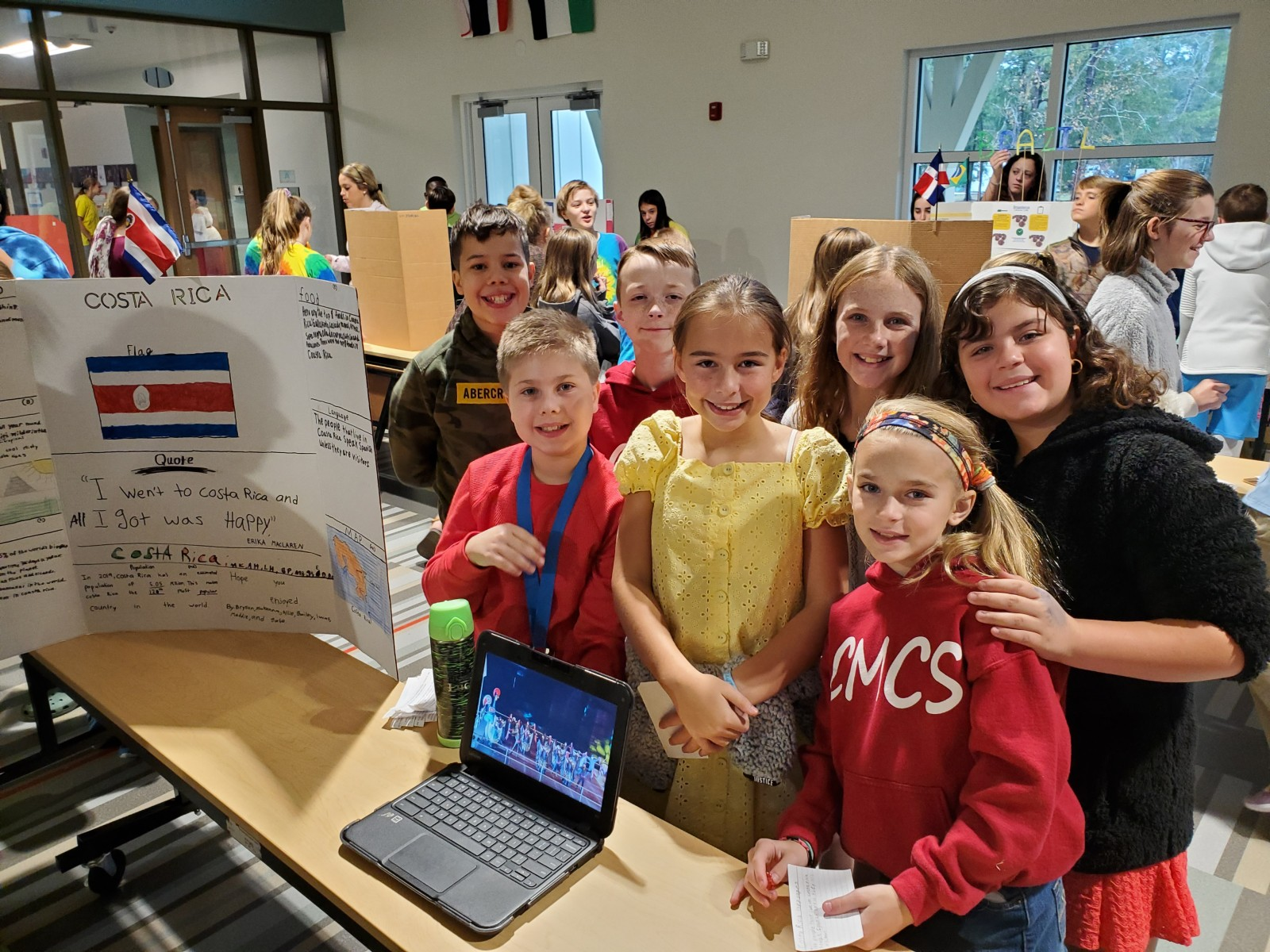 Students gather around a laptop computer and poster board at a county competition